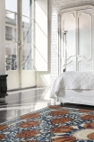 lifestyle image of Autumn Morning Rug 250cm X 150cm with large white four poster bed and glass door balcony in background