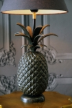 lifestyle image of Pineapple Table Lamp lit up on gold side table and white detailed wall background