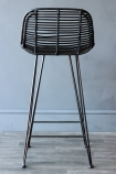 detail image of back of Black Rattan Bar Stool on grey wooden flooring and dark wall background