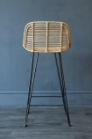 Detail image of back of Blonde Rattan Bar Stool on grey wooden flooring and dark wall background