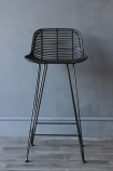 detail image of front of Black Rattan Bar Stool on dark wooden floor and dark wall background