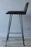 detail image of side view of Black Rattan Bar Stool on dark wooden flooring and dark wall background