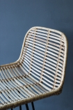 Detail image of seat on Blonde Rattan Bar Stool with dark wall background