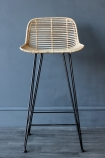 Detail image of front of Blonde Rattan Bar Stool non grey wooden flooring and dark wall background