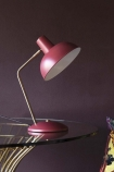 Lifestyle image of the Retro Desk Lamp - Berry Red on glass coffee table and dark purple wall background