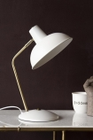 Lifestyle image of the Retro Desk Lamp - Matt White on marble table with mug and ornament in background on dark wall
