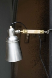 Lifestyle of retro style directional clamp task light on wall with distressed metal background
