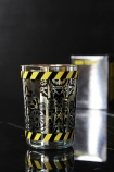 lifestyle image of Ritzenhoff Gin & Tonic Glass - Studio Job with black cogs and black and yellow border on top and bottom with box in background on black table