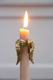 Close-up image of the Gold Angel Wings Candle Ornament on a lit candle