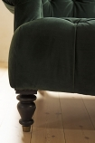 Close-up image of leg of the Two-Seater Forest Green Velvet Sofa on pale wooden floor
