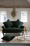 Lifestyle image of the Two-Seater Forest Green Velvet Sofa with cushions and Set Of 2 Circular Circus Nesting Tables and Shimmering Shell Disc Chandelier