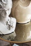 detail image of top of Antiqued Mirror Side Table with white geisha bust and pale flower pot