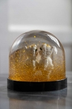 Image of the Gold Eskimo Kiss Snow Globe with glitter settling