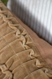 Close-up image of the top of the Camel Ruched Velvet Cushion