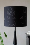 Lifestyle image of the Linea Face Design Pendant & Lamp Shade - Black With Gold Interior on a lamp