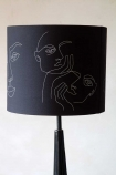 Another angle of the Linea Face Design Pendant & Lamp Shade - Black With Gold Interior on a lamp