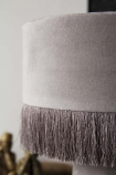 detail image of All Over Velvet Table Lamp With Fringe - Ice Grey with Three Wise Monkey Ornaments - Antique Bronze in background and pale grey wal background