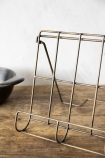 Close-up image of the Antique Brass Finish Wire Cookbook Holder on wooden surface with white wall background