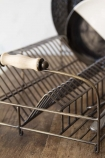 Close-up detail image of the Antique Brass Finish Wire Dish Rack with black and white dishes inside on wooden surface