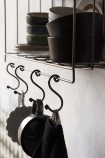 Close-up detail image of the hooks on the Antique Brass Coloured Wire Wall Rack & Hooks illed with bowls and mugs hanging on hooks on white wall background
