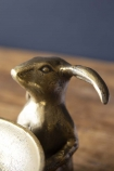 detail image of head of Antique Brass Effect Bunny Trinket Bowl on wooden table with dark wall background