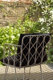 Lifestyle image of the back of the Bamboo Link Armchair With Black Noir Seat Cushion in garden background