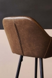 detail image of the seam on the back of the Faux Leather Bar Stool With Zig Zag Stitching - Brown with contrasting wall background