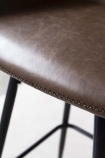 detail image of the material on the Faux Leather Bar Stool With Zig Zag Stitching - Brown with pale background