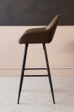lifestyle image of side view of Faux Leather Bar Stool With Zig Zag Stitching - Brown on pale wooden flooring and contrasting wall background