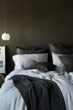 lifestyle image of Olivia Soft Linen Frill Cushion - Slate Grey on bed with white duvet ad grey blanket and pillows and white ceiling light above black and white typography print leaning on grey wall background