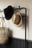 Close-up image of the coat hooks on the Industrial-Style Hallway Storage Coat Rack with hats and bag hung on hooks with pale wall background