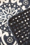 detail image of the black Modern Woven Rattan Dining Chair against the RSG black mandala round rug