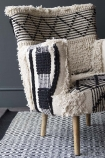 detail image of Boho Woven Armchair on grey patterned rug and dark grey wall background
