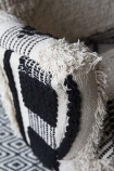 detail image of arm of Boho Woven Armchair on patterned rug