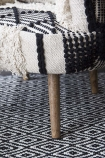 detail image of leg of Boho Woven Armchair on patterned rug background