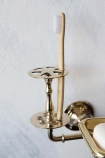 Close-up detail image of the toothbrush holder on the Brass Trio 3-in-1 Bathroom Accessory on white wall background
