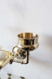 Close-up detail image of the pot ideal for toothpaste on the Brass Trio 3-in-1 Bathroom Accessory on white wall background