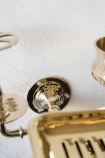 Close-up detail image of the wall fixing on the Brass Trio 3-in-1 Bathroom Accessory on white wall background