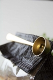 detail image of scoop on Brass Finish Coffee Scoop With Clip on pil eof napkins with white wall background