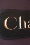 Close-up detail image of the Carved Champagne Sign on purple wall background