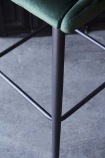 detail image of legs on Tall Casino Velvet Bar Stool - Rich Green with grey flooring background