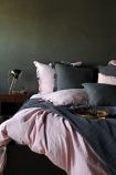 lifestyle image of Olivia Soft Linen Frill Cushion - Slate Grey on bed with pink duvet and grey blanket and pillows and breakfast on tray with wooden side table and metal table lamp with grey wall background