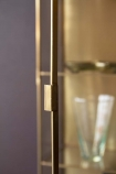 Close-up detail image of the door ajar on the Brass & Glass Wall-Mounted Display Cabinet on dark wall background