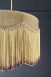 Close-up detail image of the wavy fringe on the Bespoke Inca Gold Silk Tiffany Lamp Shade on dark wall background
