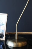 detail image of base of Grace Black & Gold Table Lamp on black table with picture frame and dark wall background