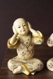 Close-up detail image of the Hear No Evil Monk on wooden surface and dark wall background