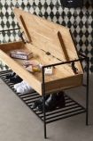 Lifestyle view of the Industrial-Style Iron & Wood Storage Bench with open bench angled with a monochrome patterned background