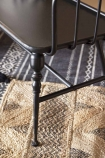 Close-up detail image of the Industrial-Style Black Metal Two-Seater Bench leg on black patterned floor and rattan rug