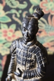Close-up detail image of the Kneeling Qin Dynasty Figure Ornament with Rockett St George Oriental Garden Wallpaper in background