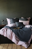 lifestyle image of Olivia Soft Linen Frill Cushion - Rose Pink on bed with pink and grey duvet and pillows and breakfast on tray with wooden side table and metal table lamp and grey wall background